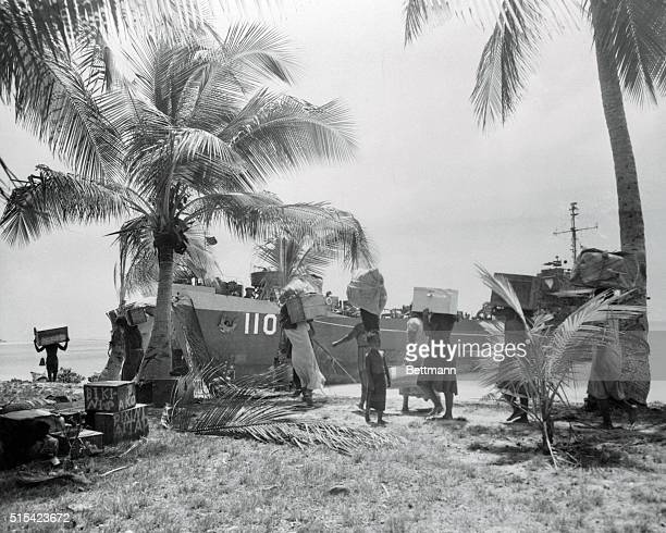 Natives of Bikini Atoll in the Pacific scene of the planned ArmyNavy atom bomb test scheduled for May carry their belongings down to the beach as...