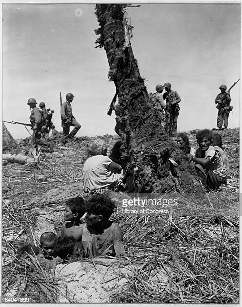 Natives of Eniwetok Island hide in foxholes while American marines patrol the area Marshall Islands 1944