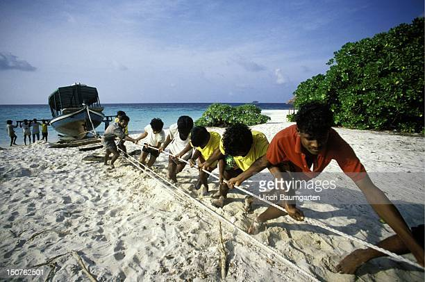 Natives pulling a boat on the beach on the island Fesdu
