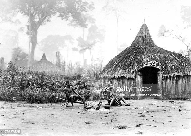 Natives sit near their hut home outside the Ituri Forest in Congo. Circa 1930.