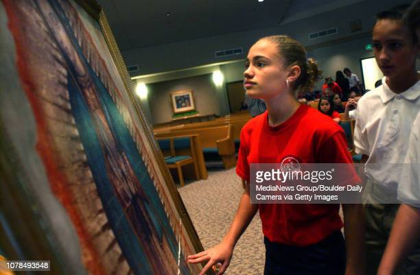 Nativity of Our Lord student Amanda Welder touches the photographic replica of the Lady of Guadalupe painting from Mexico as she and other students...