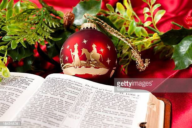 nativity red christmas ornament.  open bible. garland. st. luke. - manger stock photos and pictures