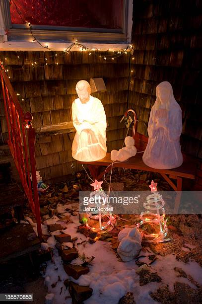 Nativity scene along with other Christmas decorations and an American flag, in front of a residence in Greenfield, MA