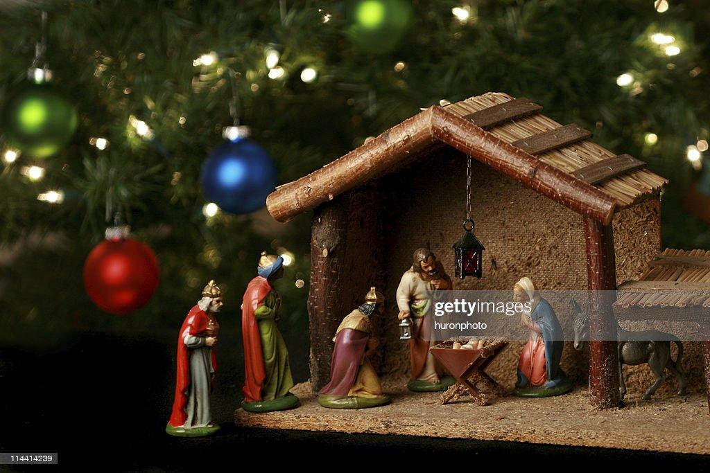 Nativity scene next to a Christmas tree : Stock Photo