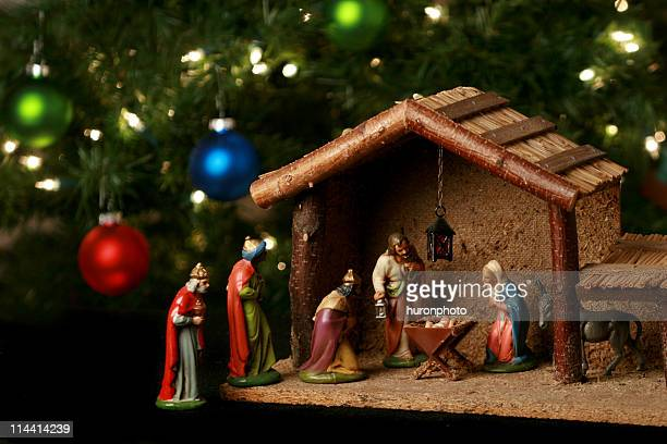 nativity scene next to a christmas tree - manger stock photos and pictures