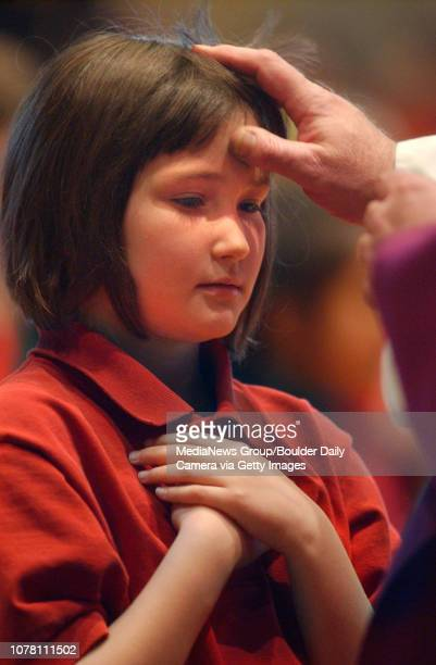 Nativity School second grader Abigail Brich receives ashes on her forehead for Ash Wednesday from Father John McCormick at Navitvity of Our Lord...