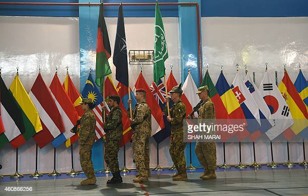 Led International Security Assistance Force soldiers carry flags during a ceremony marking the end of ISAF's combat mission in Afghanistan at ISAF...