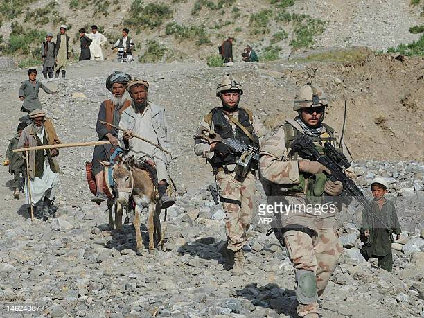 NATOled International Security Assistance Force soldiers walk with Afghan villagers during a search for victims following an earthquake in a village...