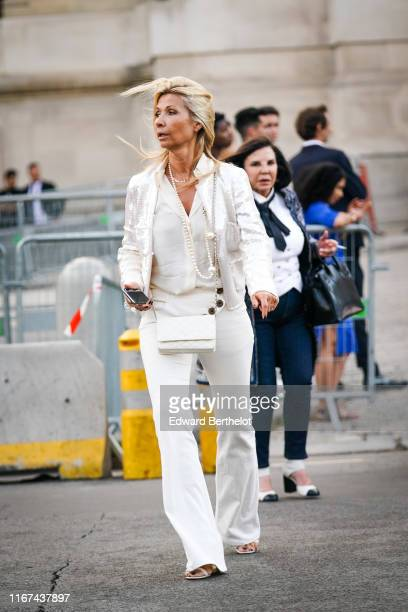 Natty Tardivel wears a pearl necklace a white shirt a white sequins embroidered jacket a white Chanel bag white pants strappy sandals outside Karl...