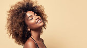 Natural Afro hair. Wide toothy smile and expression of gladness on the face of young brown skinned woman. Afro beauty.