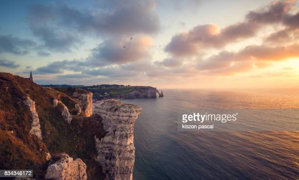 Natural arch of Etretat in Normandy ( France ) at sunset