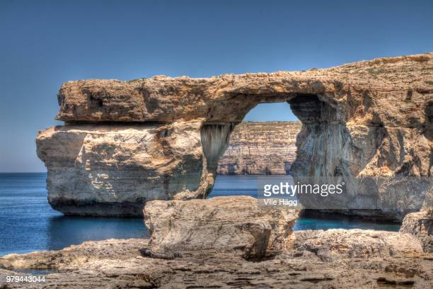 natural arch rock formation of azure window on seashore under clear sky, san lawrenz, gozo, malta - dwejra stock-fotos und bilder