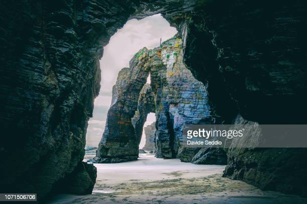natural arches during sunset on the beach of the cathedrals on the north galician coastline - rock formation stock pictures, royalty-free photos & images