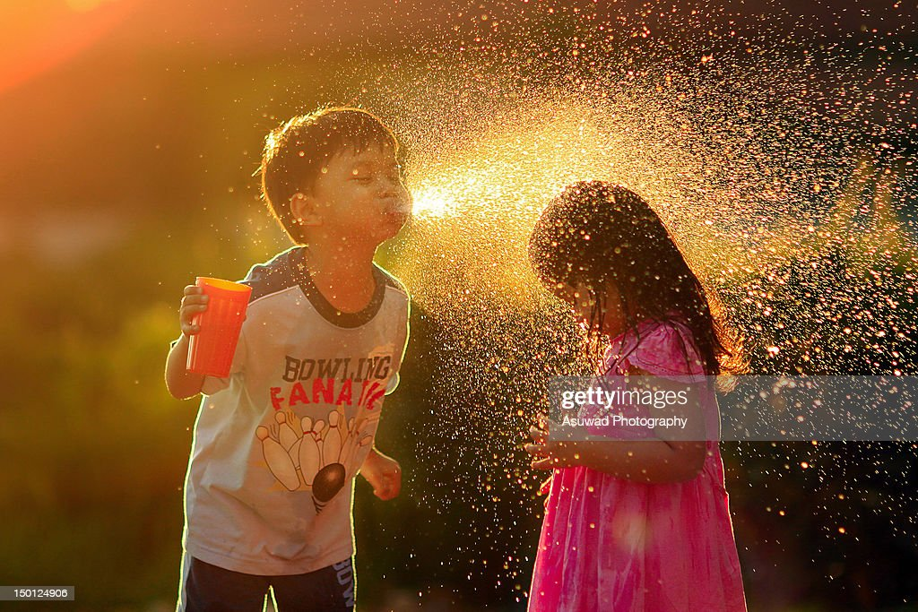 Boy and girl playing with water during sunset.