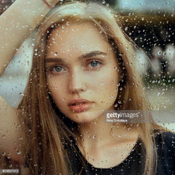 Natural blonde woman leaning on window on rainy day