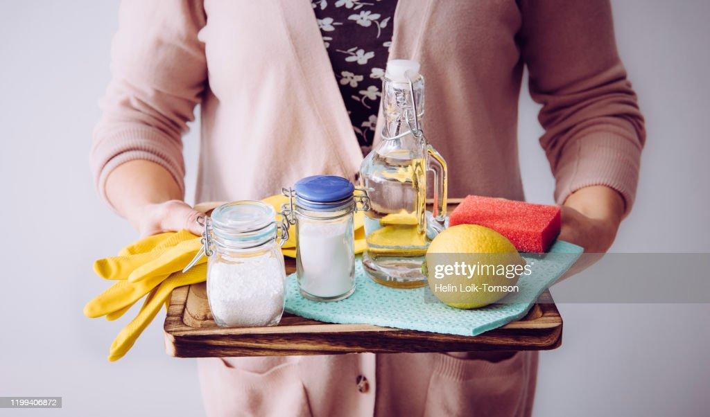 Natuurlijke reinigers concept. Vrouw met eco vriendelijke huis schoonmaak ingrediënten, witte azijn, citroen, baking soda, citroenzuur concept. : Stockfoto