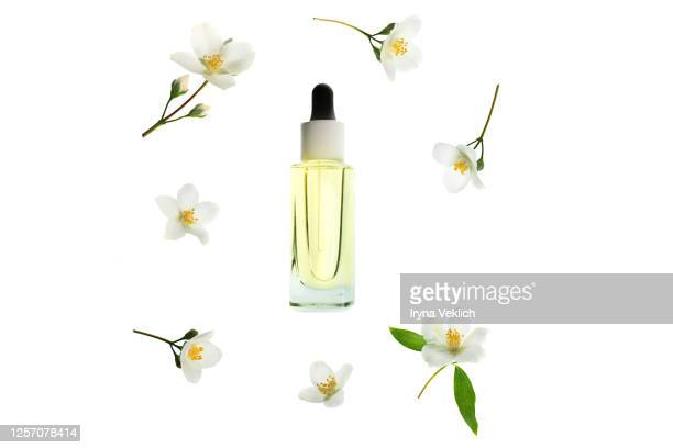 natural cosmetic product, serum or oil for the care of skin and hair with jasmine flowers, isolated. - jasmin bildbanksfoton och bilder