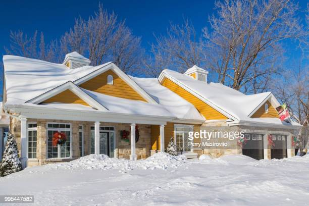Natural cut stone with yellow wood cladding country style house facade in winter