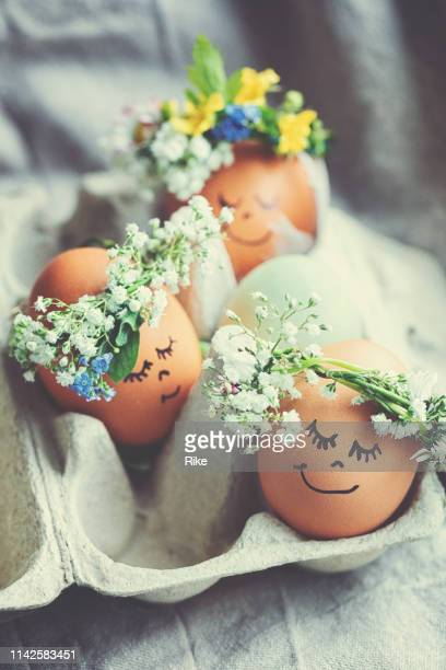 natural easter eggs with funny painted face and sweet flower wreath - pasqua foto e immagini stock