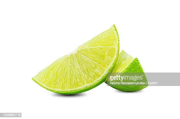 natural fresh lime with water drops and slice of green lime citrus fruit stand isolated - lime stock pictures, royalty-free photos & images