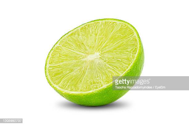 natural fresh lime with water drops and slice of green lime citrus fruit stand isolated - limette stock-fotos und bilder
