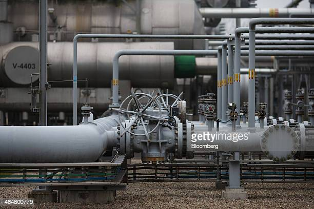 Natural gas valve wheels and pipework stands above ground at an onshore gas extraction site operated by Nederlandse Aardolie Maatschappij BV in Ten...