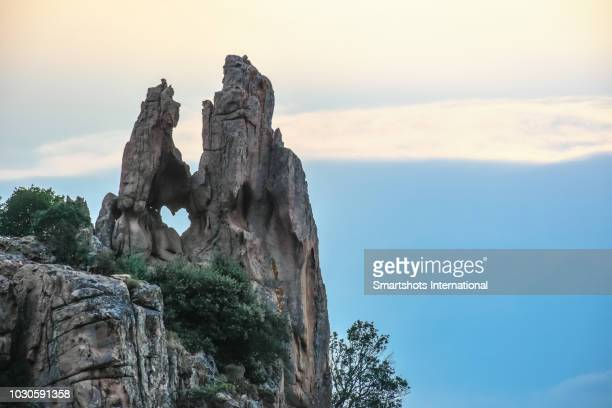 natural heart-shaped rock fracture in calanches de piana, corsica, france, a unesco heritage site - corsica stock-fotos und bilder