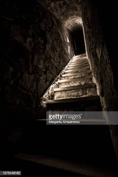 Natural light on narrow stairs leading to a closed door