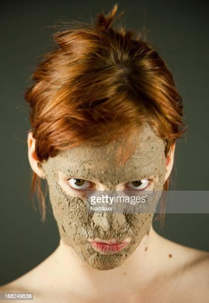 Fango naturale applicazione per la cura della pelle del viso di una donna giovane