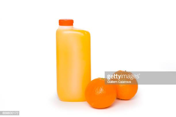 natural orange juice bottled together with oranges - fruta stock photos and pictures