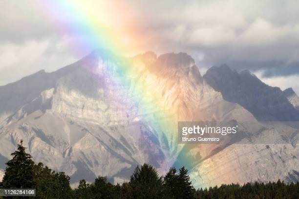 natural rainbow phenomenon against mountains - light natural phenomenon stock pictures, royalty-free photos & images