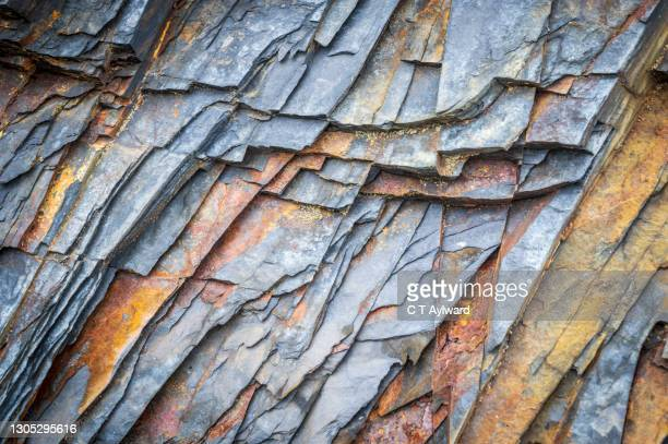 natural rock pattern rust slate beach coast - industry stock pictures, royalty-free photos & images