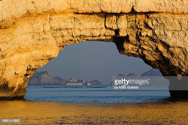 a natural sea arch framing a boater and a fort of nearby muscat, oman. - gulf of oman ストックフォトと画像