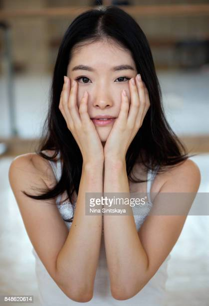 Naturally looking Japanese woman holds her face in hands