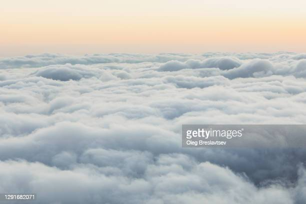 nature background of sky with room for copy space. view of low clouds from above at sunset - cloudscape stock pictures, royalty-free photos & images