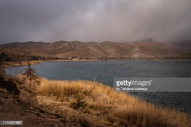 nature panorama with lac de tislit lake in the mountains during the storm, morocco, africa - wilderness area stock pictures, royalty-free photos & images