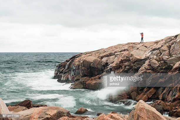 Nature photographer on coastline, woman photographing