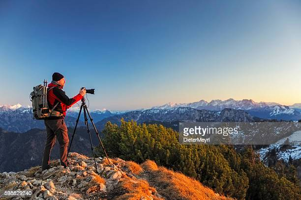 Nature photographer with tripod an backpack  in the alps
