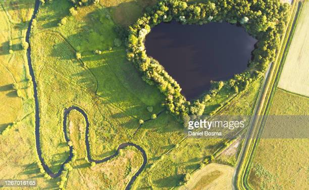 nature reserve with winding river bordering a man-made landscape - nature reserve stockfoto's en -beelden