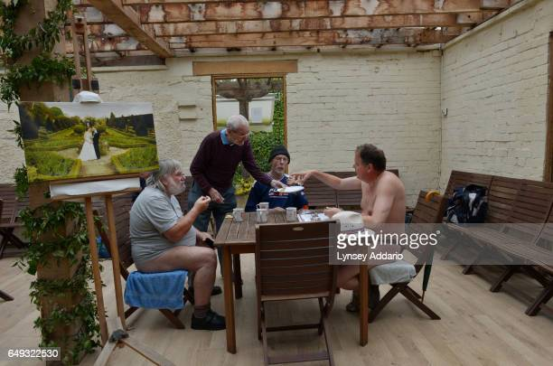 Naturists Nick Tarling Roger Monroe and Paul Pride have snacks as they gather on Clothes Optional Day in the Abbey House Gardens in Malmesbury...