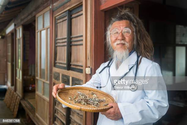 A naturopathic doctor of holding a tray of dried herbs