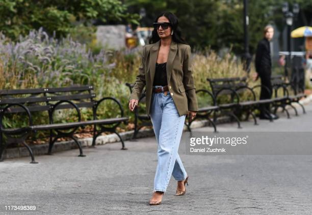 Nausheen Shah is seen wearing a green jacket black top blue jeans and black sunglasses outside the Carolina Herrera show during New York Fashion Week...