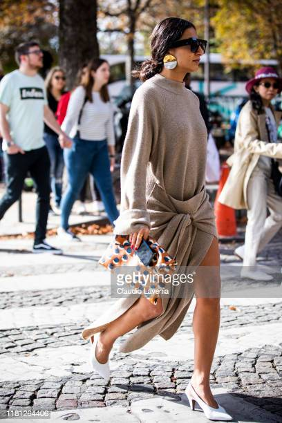Nausheen Shah, wearing a beige knitted dress, printed bag and white heels, is seen outside the Sacai show during Paris Fashion Week - Womenswear...