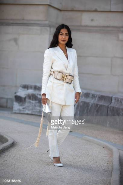 Nausheen Shah wears a white pinstripe suit jacket and pants and large belt outside the Elie Saab show at Grand Palais during Paris Fashion Week...