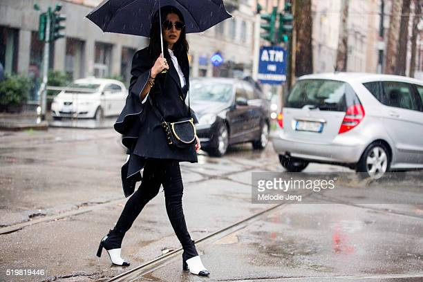 Nausheen Shah wears Spektre sunglasses a black Ellery top a fur purse and black and white heeled boots in the rain at the Dolce Gabbana show at...