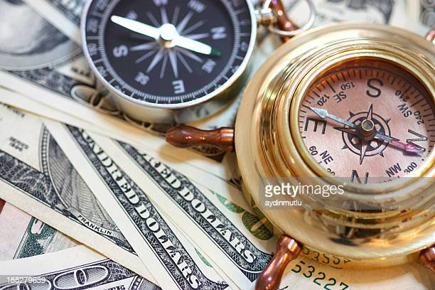 nautical compasses on top of us paper currency - dollar sign key stock photos and pictures