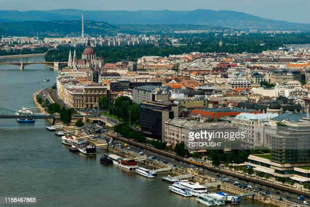 nautical vessels anchored in danube river at budapest city - hungria stock photos and pictures