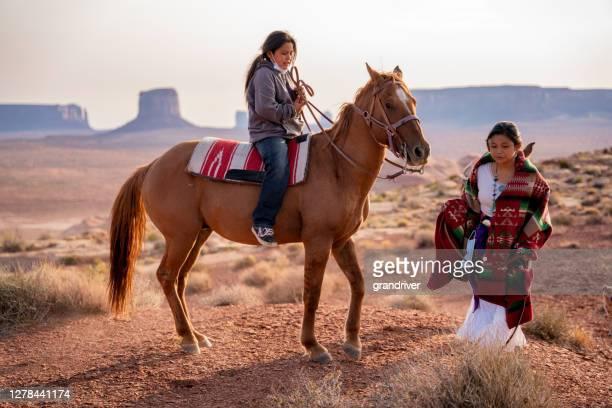navajo enfants, frère et sœur, garçon à cheval bareback avec fille marchant le long de côté dans le vaste désert dans la réserve de navajo et monument valley tribal park dans le nord de l'arizona - apache photos et images de collection
