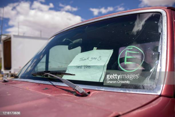 Navajo family display a note on their windshield for Navajo Nation President Jonathan Nez and his team while they distribute food, water, and...
