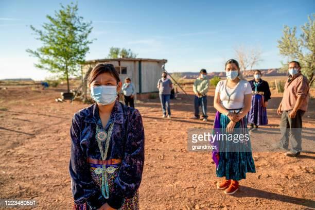 コロナウイルスパンデミック中にマスクを着用して、社会的な離散を練習するナバホの家族 - ナバホ文化 ストックフォトと画像